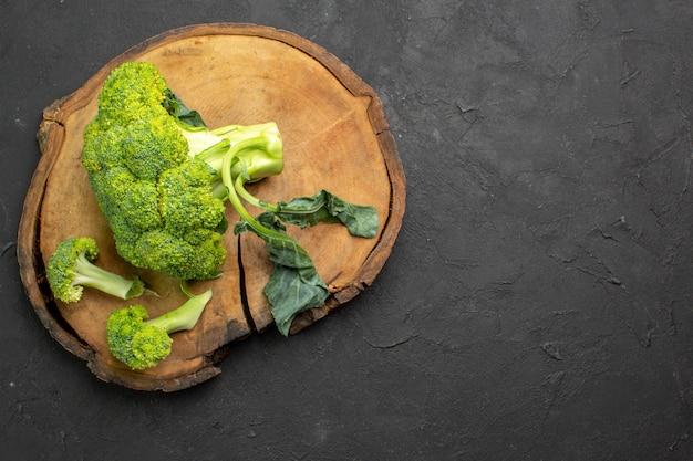 Broccoli verdi freschi di vista superiore su una salute matura dell'insalata della tavola scura
