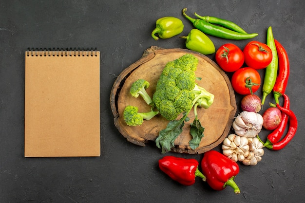 Вид сверху свежей зеленой брокколи со свежими овощами на темном столе, салат спелого цвета