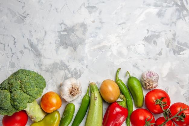 Вид сверху свежей зеленой брокколи с овощами на белом салате на полу, спелая здоровая диета