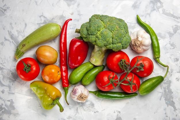 Broccoli verdi freschi di vista superiore con le verdure sulla dieta di salute matura dell'insalata della tavola bianca