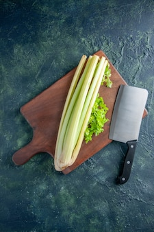 Top view fresh green celery with big knife on a dark blue surface salad health diet food meal color photo