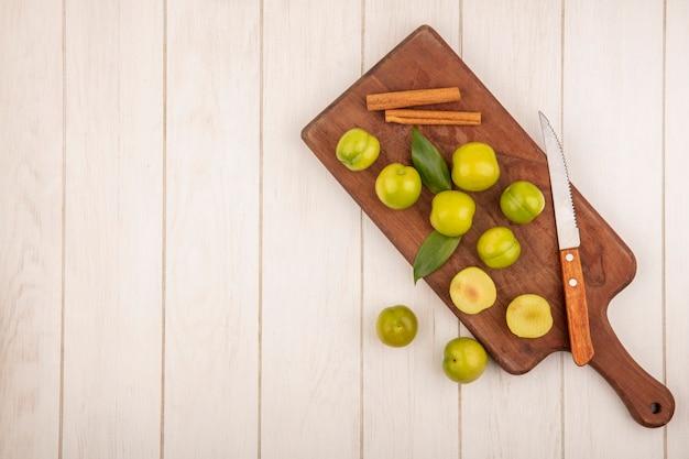 Vista dall'alto di prugna ciliegia verde fresca su una tavola di cucina in legno con bastoncini di cannella con coltello su un fondo di legno bianco con lo spazio della copia