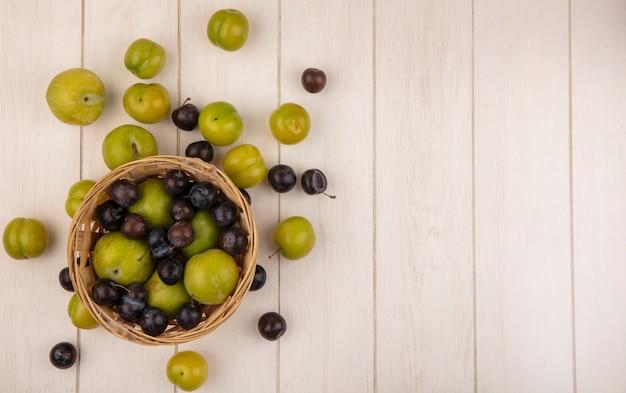 Vista dall'alto di prugne ciliegie verdi fresche su un secchio con prugnole viola scuro su un fondo di legno bianco con lo spazio della copia