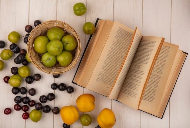 Vista dall'alto di prugne ciliegia verdi fresche su un secchio con ciliegie peachesred gialle isolate su un fondo di legno bianco