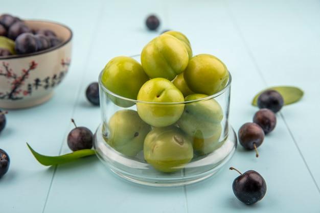 Vista dall'alto di prugne ciliegie verdi fresche su un barattolo di vetro con prugnole su una ciotola su sfondo blu