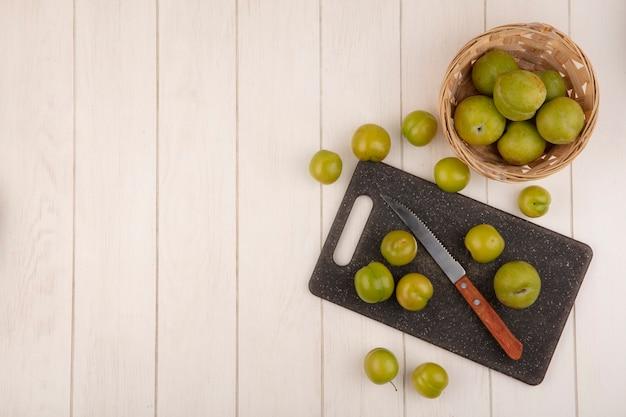 Vista dall'alto di prugne ciliegie verdi fresche su un tagliere di cucina con coltello con prugne ciliegia su un secchio su un fondo di legno bianco con spazio di copia