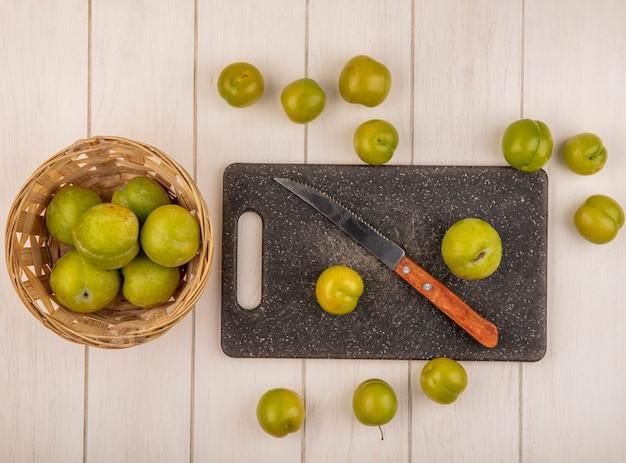 Vista dall'alto di prugne ciliegie verdi fresche su un tagliere da cucina con coltello con prugne ciliegia su un secchio su un fondo di legno bianco