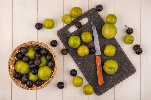 Vista dall'alto di prugne ciliegia verde fresco su un tagliere di cucina con coltello con prugne ciliegia e prugnole su un secchio su un fondo di legno bianco