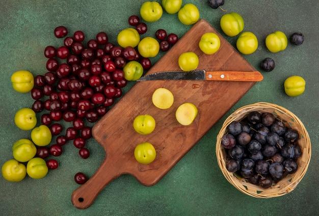 Vista dall'alto di prugne ciliegie verdi fresche su una tavola da cucina in legno con coltello con ciliegie rosse con prugnole su un secchio su sfondo verde