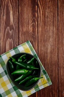 Top view of fresh green chili peppers in a bowl on plaid napkin on wooden rustic background with copy space