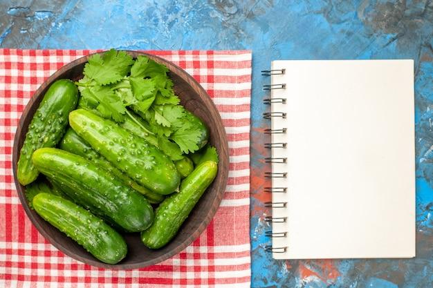 Vista dall'alto cetrioli verdi freschi all'interno del piatto su sfondo blu