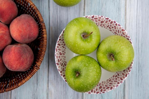 Vista dall'alto di mele fresche verdi e deliziose sulla ciotola con le pesche sul secchio su legno grigio