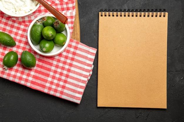 Vista dall'alto feijoa verde fresco con crema e blocco note su frutta esotica di superficie scura dolce