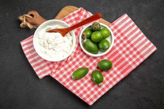 暗い表面のフルーツエキゾチックな健康まろやかなクリームとトップビューの新鮮な緑のフェイジョア