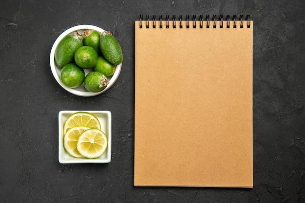 暗い表面の果物野菜柑橘類のまろやかな植物の木にレモンスライスとメモ帳を備えた上面図新鮮な緑のフェイジョア