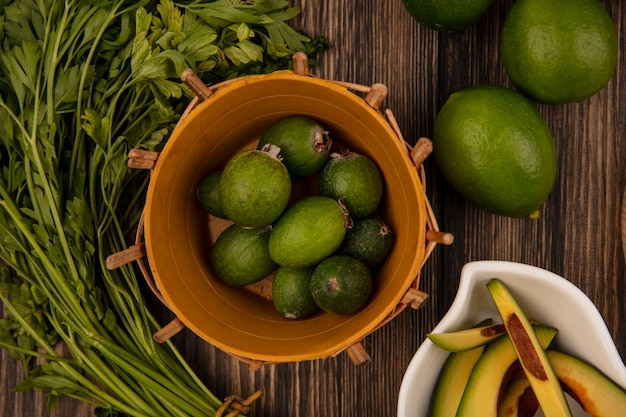 Top view of fresh green feijoas on a bucket with avocado slices on a bowl with limes and parsley isolated on a wooden background
