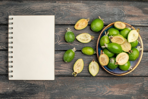 木製の素朴な机の上のプレートの内側のトップビュー新鮮な緑のフェイジョアカラー写真ジュース熟した酸っぱい