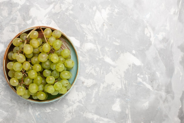 Top view fresh green grapes inside  on white surface
