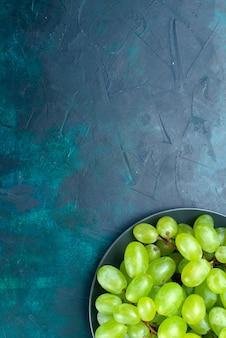 水色の机の上にジューシーでまろやかな果物のトップビューの新鮮な緑のブドウ。