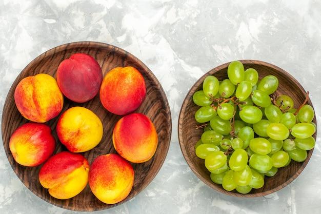 明るい白い机の上に桃とまろやかでおいしい新鮮な緑のブドウの上面図
