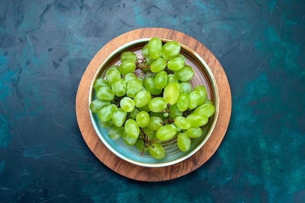 상위 뷰 신선한 녹색 포도 진한 파란색 책상에 접시 안에 부드러운 달콤한 과일.