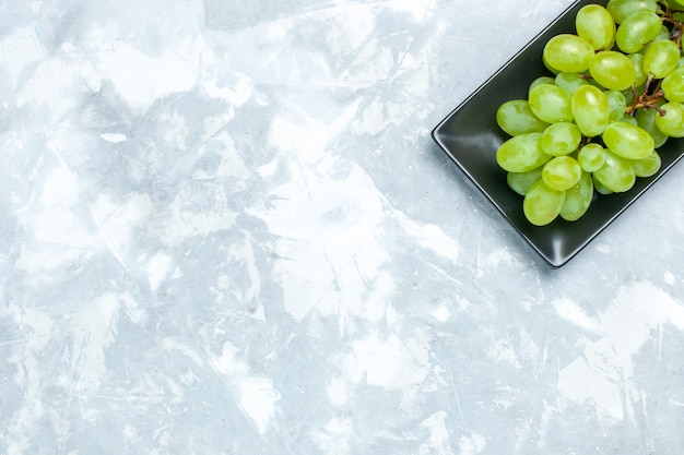Top view fresh green grapes mellow juicy fruits inside black form on light desk.
