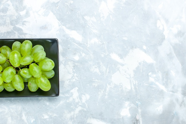 Top view fresh green grapes mellow juicy fruits inside black form on the light desk.