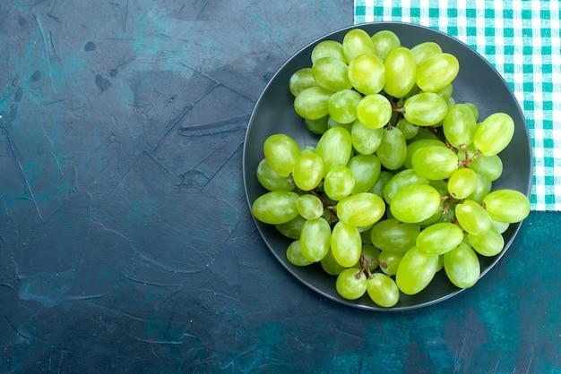 Vista dall'alto uva verde fresca mellow frutti succosi all'interno del piatto sullo scrittorio blu scuro.