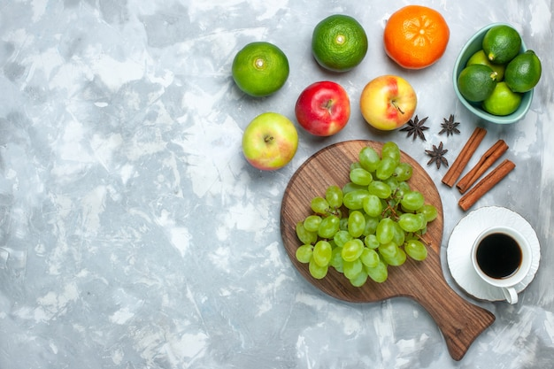 Вид сверху свежий зеленый виноград сочные сочные фрукты с корицей, лимонами и чаем на светлом столе.