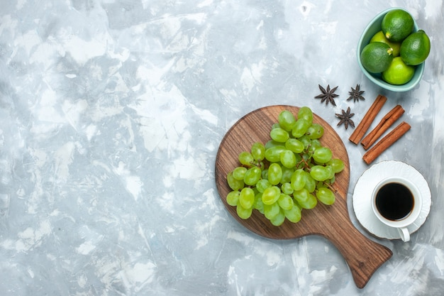 Top view fresh green grapes mellow juicy fruits with cinnamon lemons and tea on light desk.