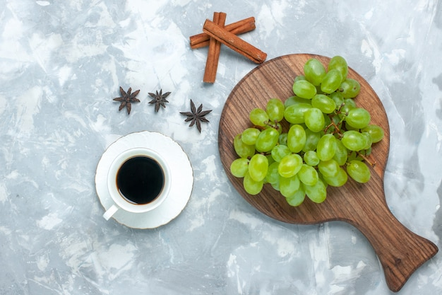 Top view fresh green grapes mellow juicy fruits with cinnamon and tea on the light desk.