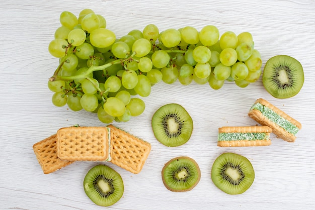 A top view fresh green grapes sour juicy and mellow with cookies and kiwis fruit ripe plant green