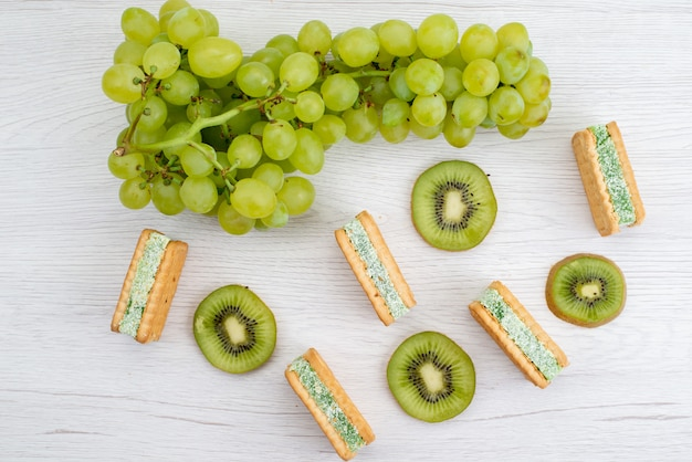 A top view fresh green grapes sour juicy and mellow with cookies and kiwis on the white background fruit ripe plant