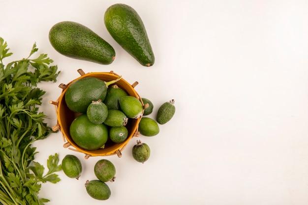 Vista dall'alto di fresche limette verdi su un secchio con avocado feijoas e prezzemolo isolato su una superficie bianca con spazio di copia