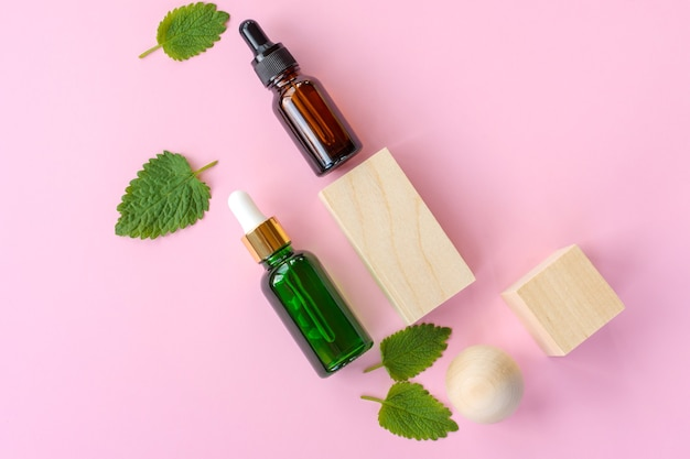 Top view of fresh green mint or spearmint leaves and glass dropper bottles of mint essential oil on pink background. natural herbal medical aromatic plant concept.