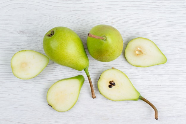 A top view fresh green pears sliced and whole on the white background  fruit color