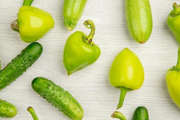 上面図新鮮なピーマンと緑のきゅうりとトマトの白い机の色熟したサラダ写真食事ホット