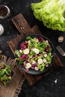 暗いボウルでトップビュー新鮮なグリーンサラダ