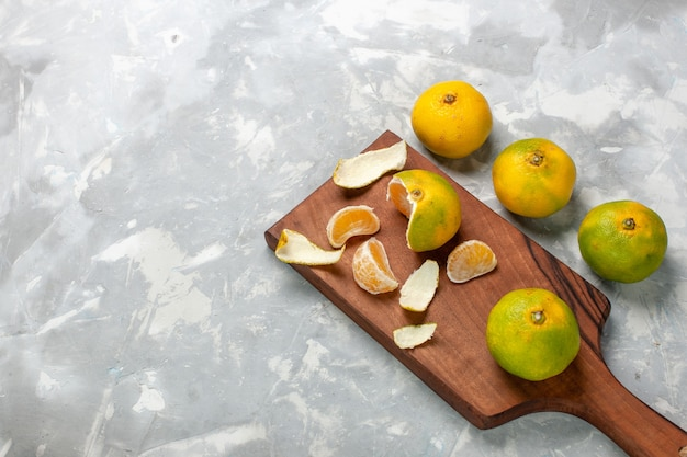 Вид сверху свежие зеленые мандарины, целые кислые и спелые цитрусы на светло-белом столе.