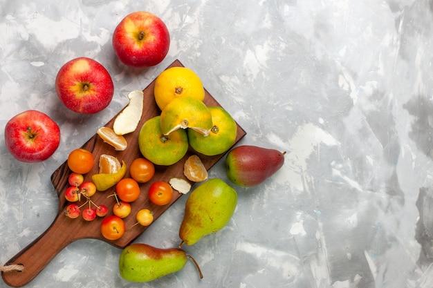 Вид сверху свежие зеленые мандарины целые кислые и спелые цитрусы с яблоками на светлом белом столе.