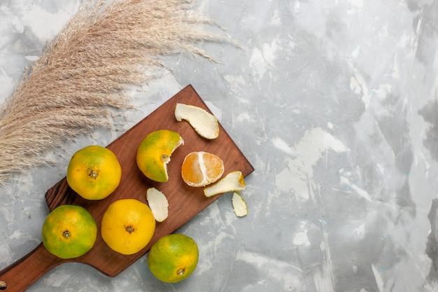 Vista dall'alto mandarini verdi freschi interi agrumi acidi e pastosi su sfondo bianco chiaro.