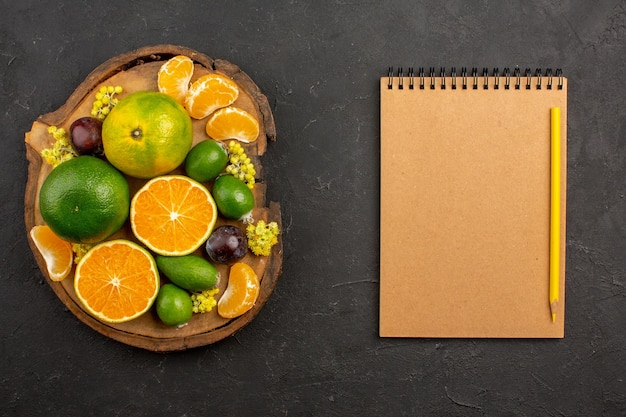 Top view of fresh green tangerines with feijoas on dark table