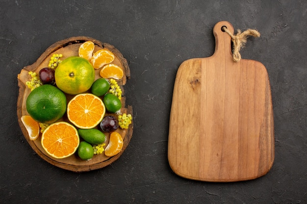 Top view of fresh green tangerines with feijoas on dark