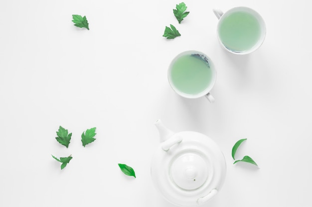 Top view of fresh green tea with tea leaves and teapot