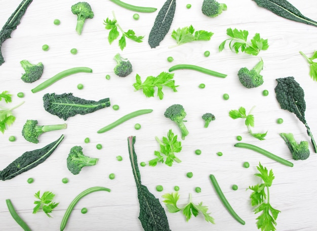 Top view of fresh green vegetables on the white wooden table