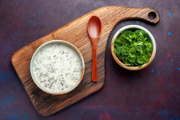Vista dall'alto di verdure fresche all'interno di una ciotola rotonda con dovga sul tavolo scuro, verdura fresca cibo verde