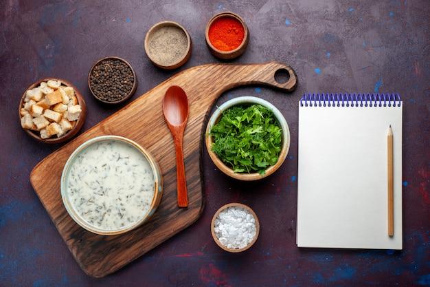Vista dall'alto di verdure fresche all'interno della ciotola rotonda con blocco note a forma di colomba e fette biscottate sul tavolo scuro, verdura fresca di cibo verde