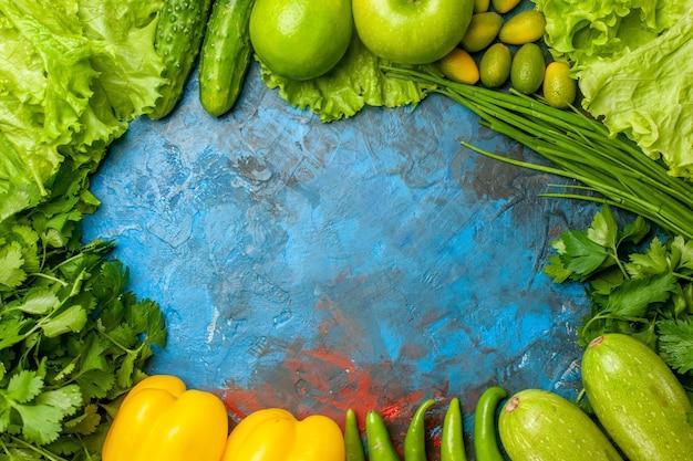 Вид сверху свежей зелени с яблоками, огурцами и другими продуктами на синем фоне