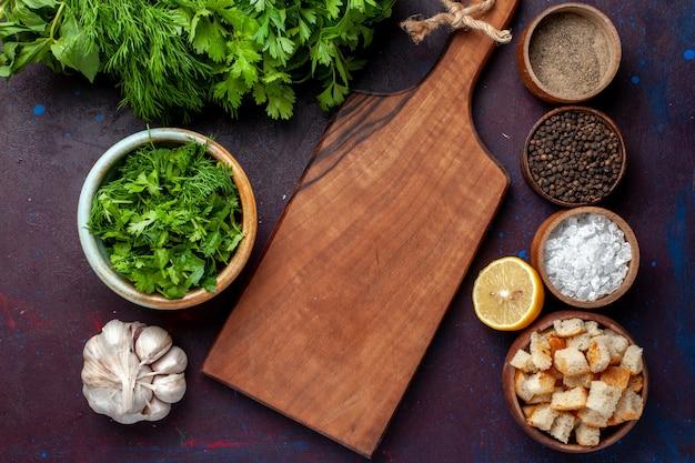 Вид сверху свежей зелени с чесночными сухарями и приправами на темном столе, суп, зеленый ужин