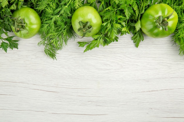 Top view fresh greens with green tomatoes on white background